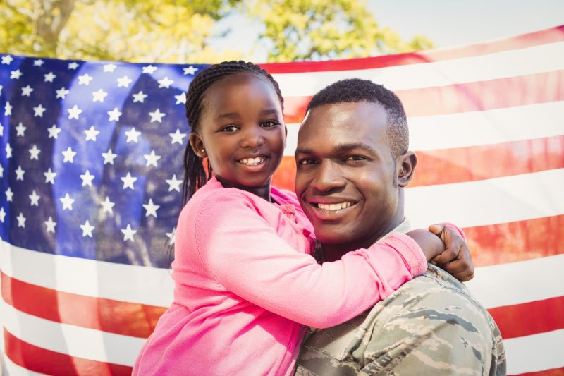 Male veteran with daughter in a pink hoodie in front of an American flag